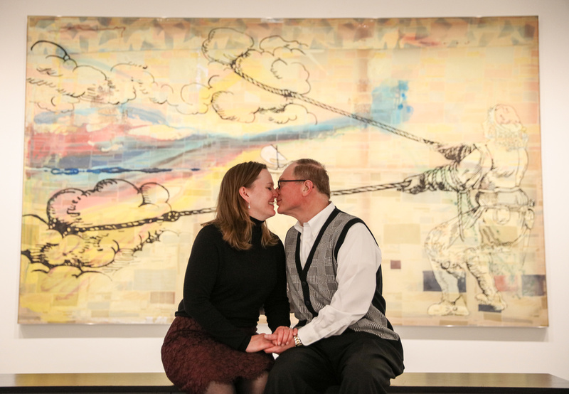 Engagement photography, a couple snuggles on a bench in front a watercolor piece of artwork.