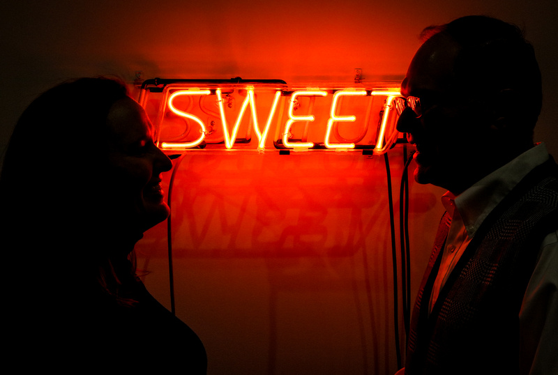 "Engagement photography, a red, neon sign that says ""sweet"" with a couple in silhouette."