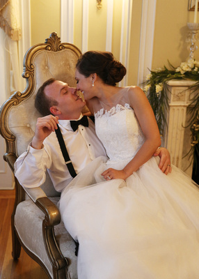 Bride and groom sit together on one ornate chair; bride leans in for a kiss. 5 reasons you need to click with your photographer.