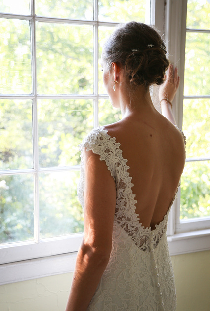 Wedding photography, a bride looks out the window wearing a low back lace gown.