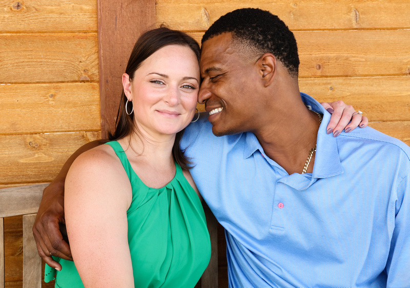 Engagement photography: a woman in a green dress smiles at the camera while her fiancé looks at her with love.