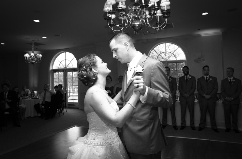 Wedding photography, a bride and groom share their first dance with the wedding party watching admiringly.