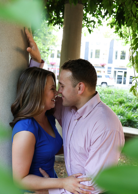 Man in pink shirt leans in for a kiss from his laughing fiancé. engagement photography