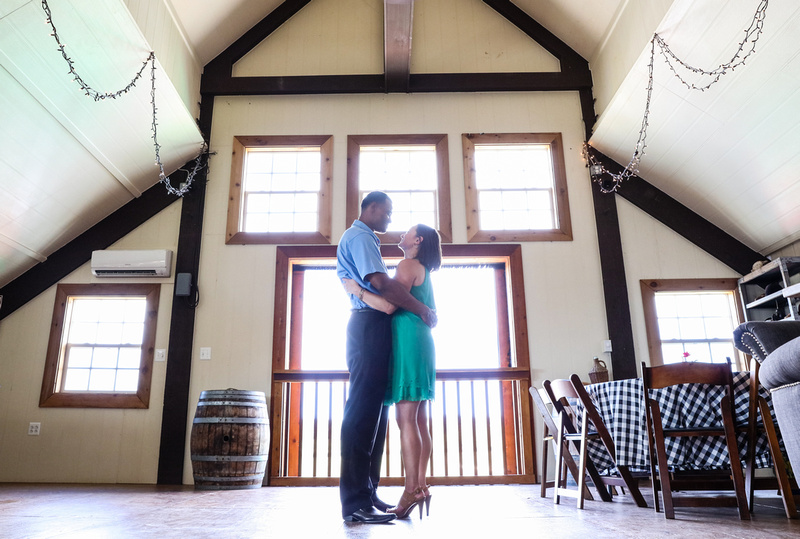 Engagement photography: a couple stands together in a barn with a big window, looking at each other lovingly.