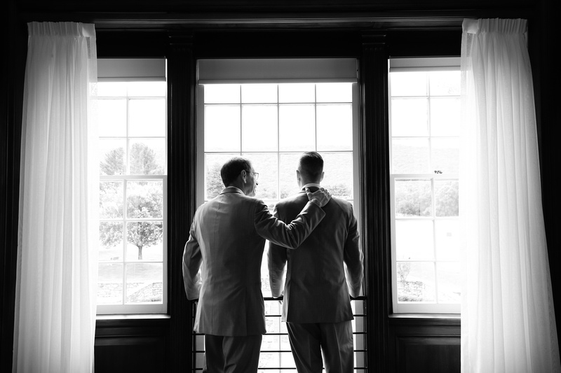 Wedding photography, a father and son lovingly stand together looking out a window at the wedding venue.