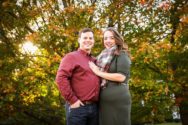 Engagement photography: a young couple smiles while standing in front of a beautiful fall tree.