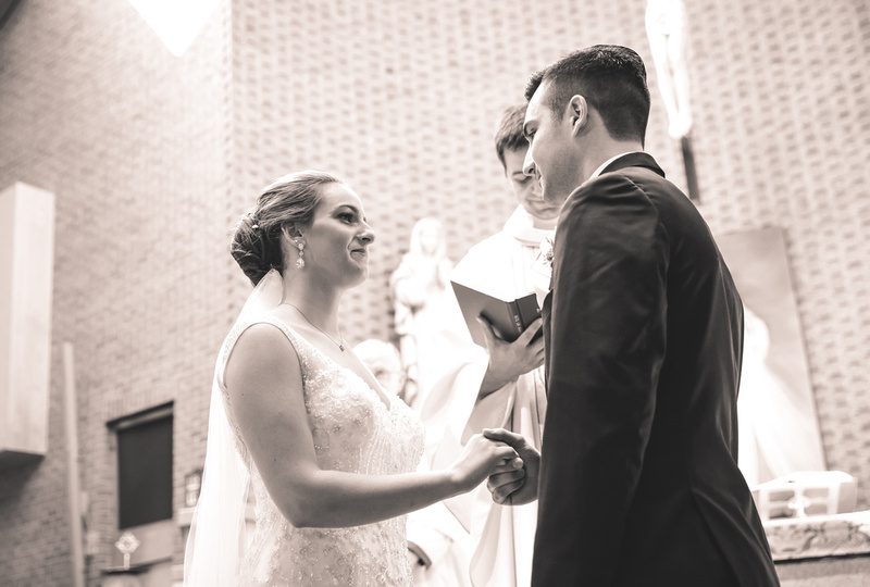 Wedding photography, a bride and groom gaze lovingly into each other eyes. They are holding hands in front of the alter.