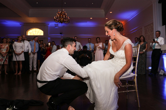 Wedding photography, the bride laughs while the groom reaches up her dress for the garter.