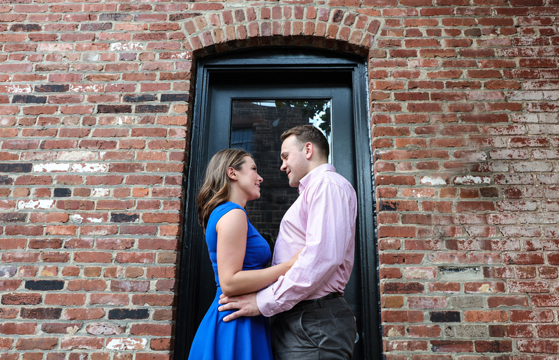 A couple faces each other smiling in front of a brick wall with a black door. She wears a blue dress, he wears a pink shirt. engagement photography
