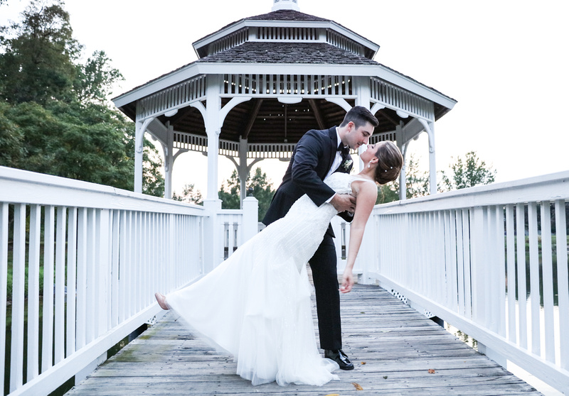 Wedding photography, a groom dips his bride while standing in front of a white gazebo.