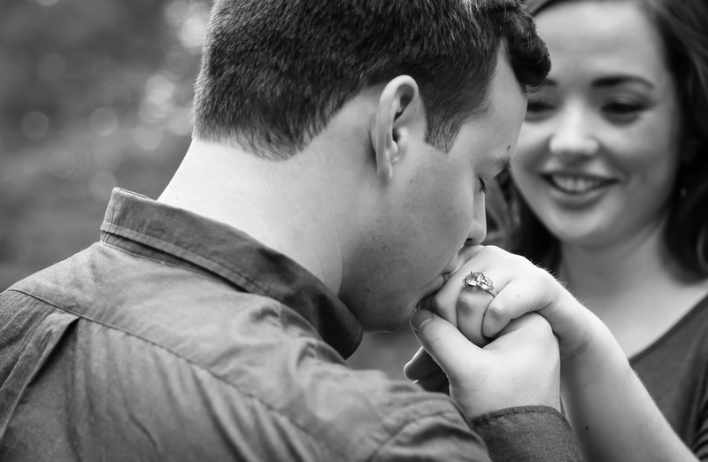 Engagement photography: a young man kisses his fiancées hand and engagement ring while she smiles.