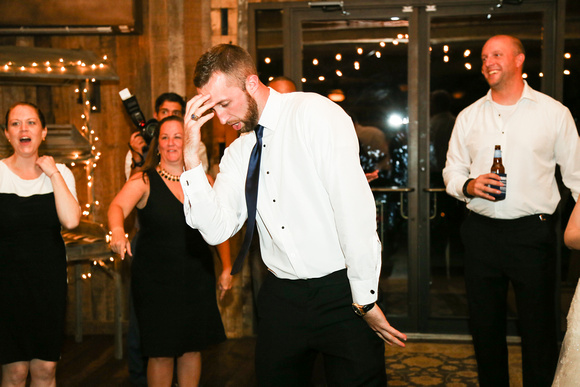 Wedding photography, a groomsman dances dramatically. The groom is smiling behind him.