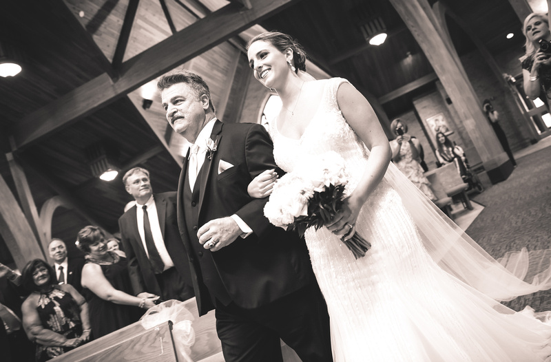 Wedding photography, a bride and her father walk down the aisle. She is smiling as she looks at her groom.