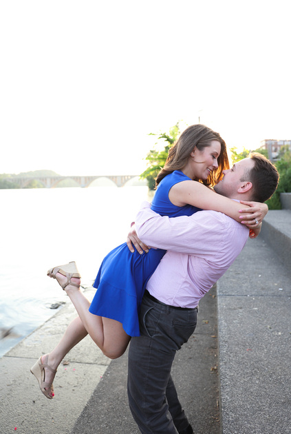 A young man picks up a young woman in a blue dress, they are by the waterfront. engagement photography