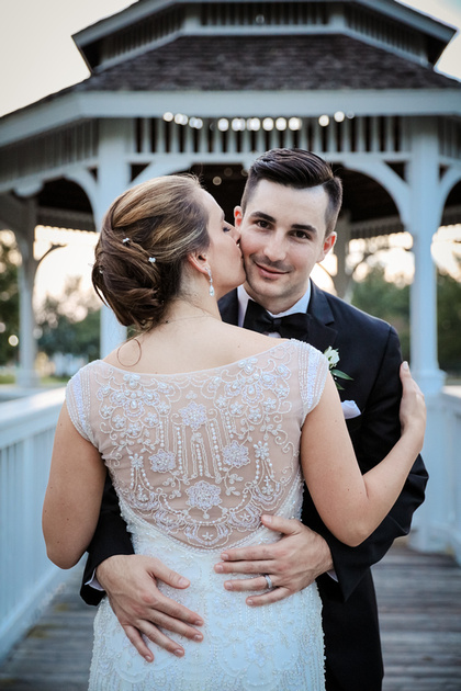 Wedding photography, a groom smiles at the camera while his bride kisses his cheek She wears an embroidered gown.