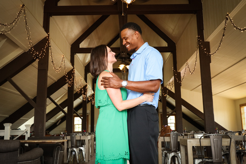 Engagement photography: a couple stands together in a barn with twinkle lights, looking at each other lovingly.