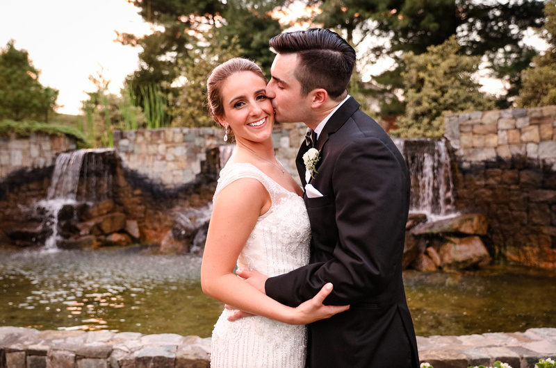 Wedding photography, a bride and groom stand in front of a large fountain. He kisses her cheek while she smiles.