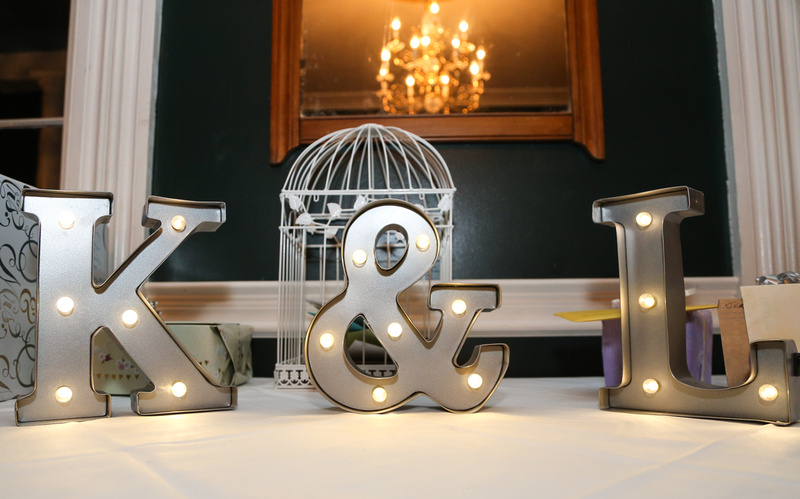 Wedding photography, the letters K and L on a table with a gold chandelier in the mirror above them.