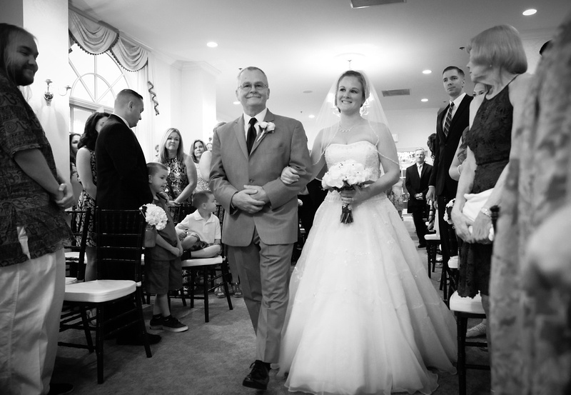 Wedding photography, a bride and her father walk down the aisle, arm in arm.