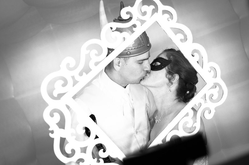 Wedding photography, a bride and groom kiss in their photo booth. She wears a black mardi gras mask, he wears Viking horns.