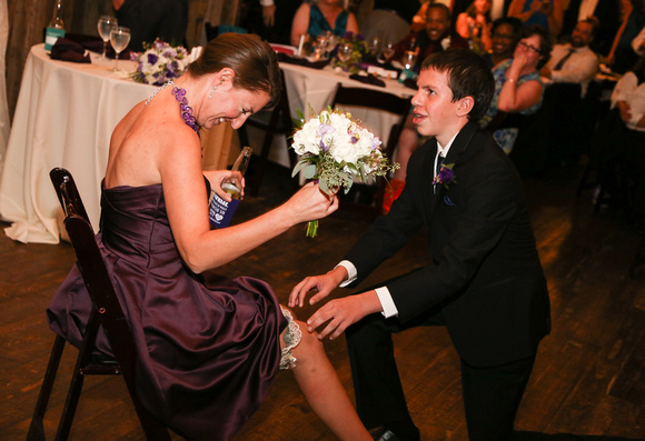 Wedding photography, a young man awkwardly puts the garter on the winner of the bouquet toss.