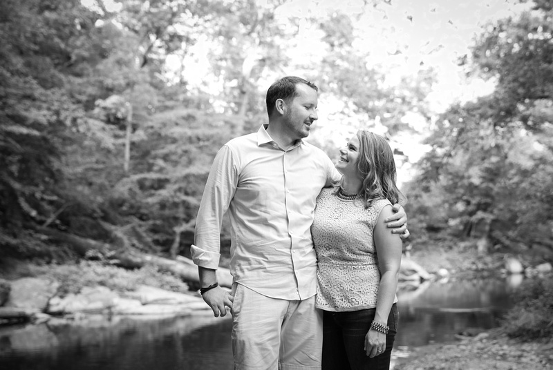 Family photography: a black and white photo of a couple embracing in front a stream in the woods.