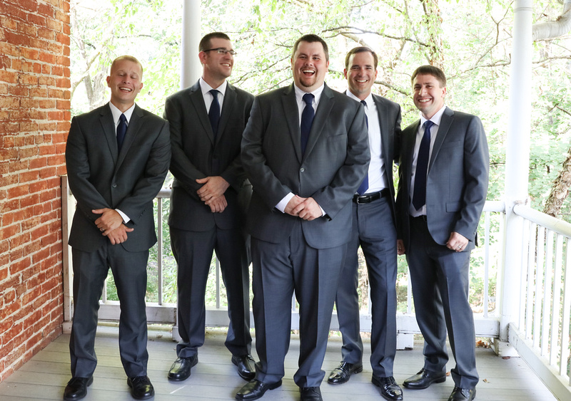 Wedding photography, a groom and his groomsmen stand on a white porch with a brick wall. They are laughing and wearing grey suits.