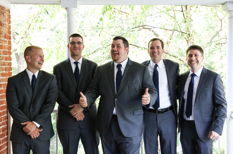Wedding photography, a joyous groom gives two thumbs up as he stands on a porch with his groomsmen.