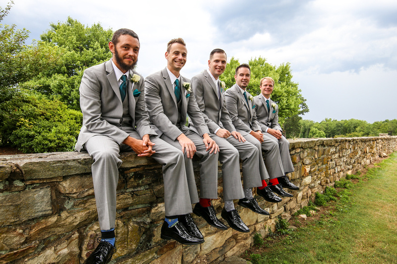 Wedding photography, a groom and his groomsmen sit on a stone wall smiling and showing off their colorful socks.