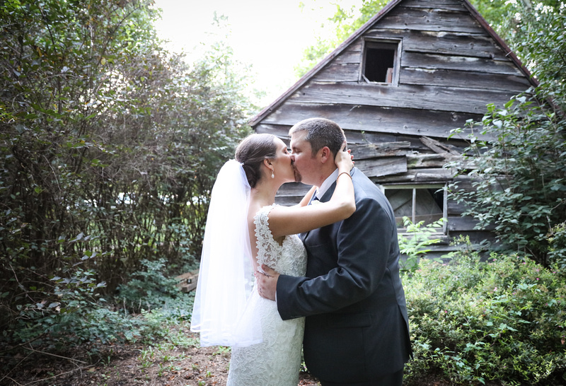 Wedding photography, a bride and groom kiss passionately in front of an antique barn in the woods.