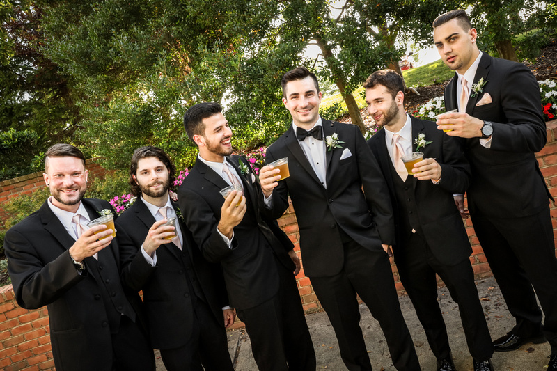 Wedding photography, a groom and his groomsmen wearing black tuxedos toast their cocktails.