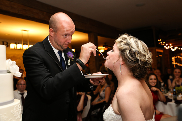 Wedding photography, the groom feeds his bride a bite of cake. She has her eyes closed with happiness.