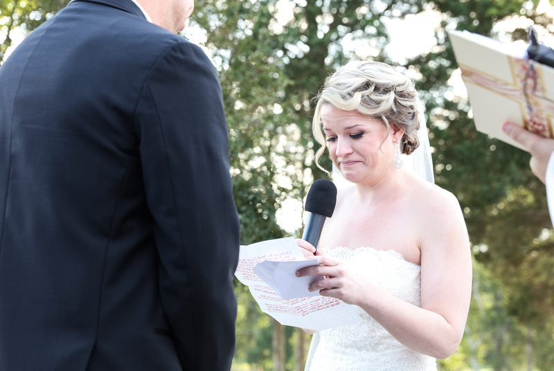Wedding photography, a bride fights back tears as she reads her wedding vows.