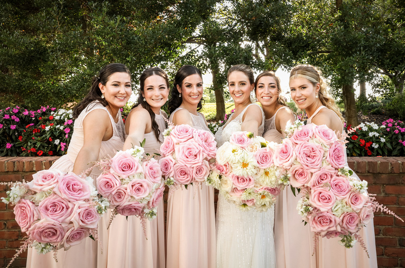 Wedding photography,  a bride and bridesmaids in pink dresses hold out their pink bouquets.