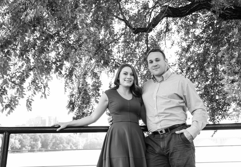 Beautiful young fiancés lean on a railing by the waterfront. A tree dips down behind them. engagement photography