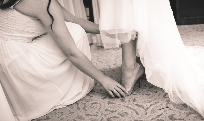 Wedding photography, a bridesmaid helps slip on the shoe of a bride.