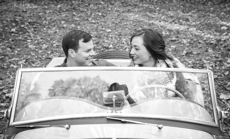 Engagement photography: a young couple sits behind the wheel of an antique car and smile at each other.