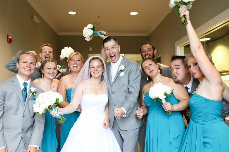 Wedding photography, an elated bride and groom celebrate with their wedding party, who is equally as excited.