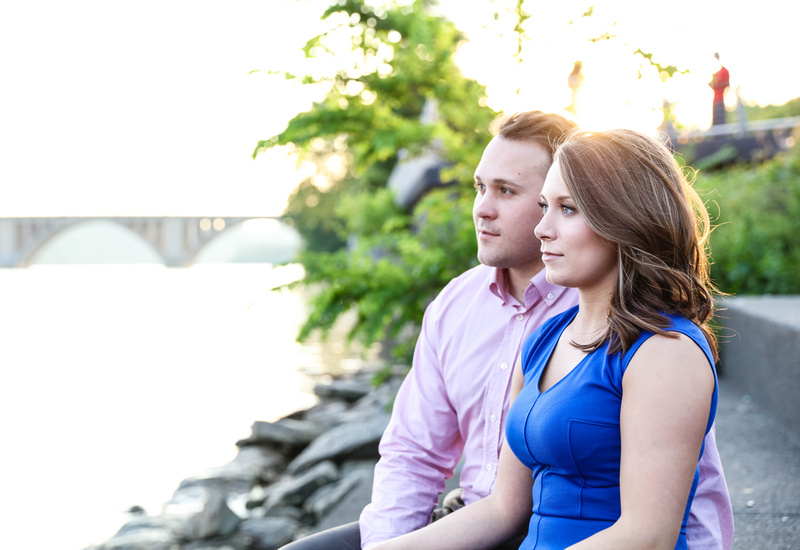 A young couple gaze out at the waterfront as they sit on the steps, with a bridge in the background. engagement photography