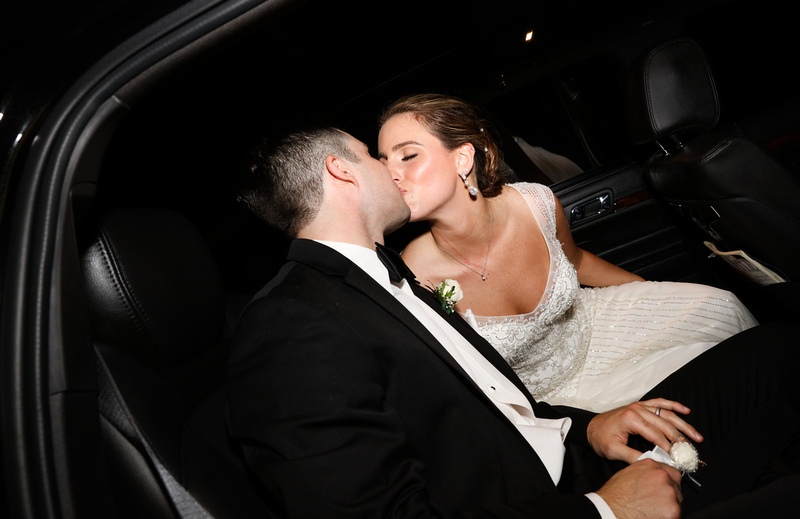 Wedding photography, the bride and groom kiss in their limo.