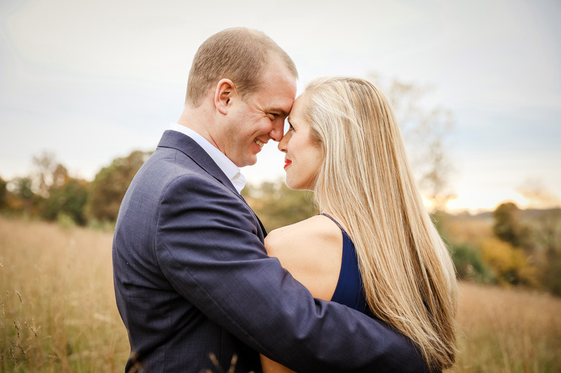 Engagement photography, a young couple place their foreheads together and smile lovingly.