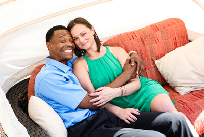 Engagement photography: a man in a blue shirt squeezes his fiancé with love while sitting on a red couch.