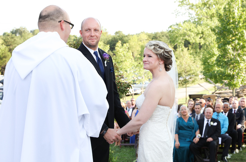 Wedding photography, a bride and groom hold hands and smile at the wedding officiant.