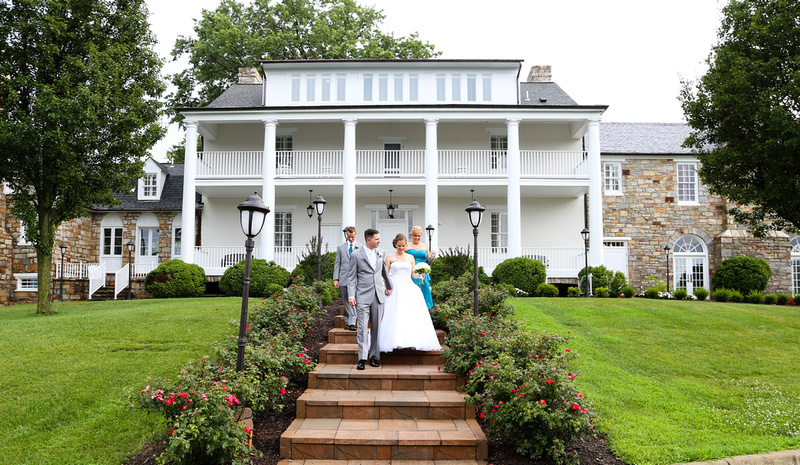Wedding photography, a bride and groom walk down the red stone steps of a large white mansion.