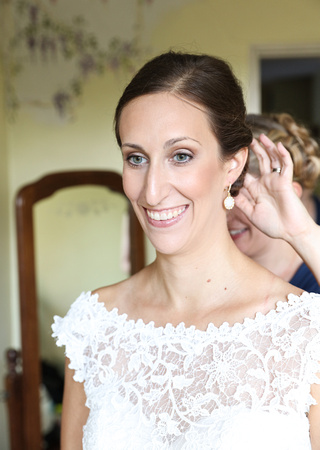 Wedding photography, a brunette bride smiles blissfully as her bridesmaid adjusts her hair.