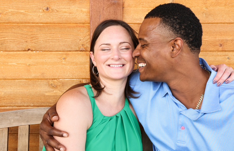 Engagement photography: a woman in a green dress laughs as her fiancé presses his face against hers and smiles.