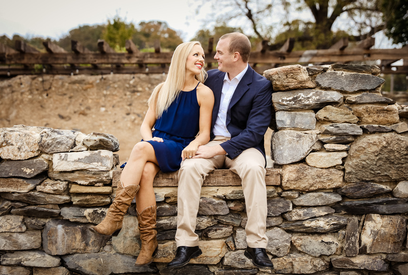 Engagement photography, a couple sits on stone wall with trees behind them.