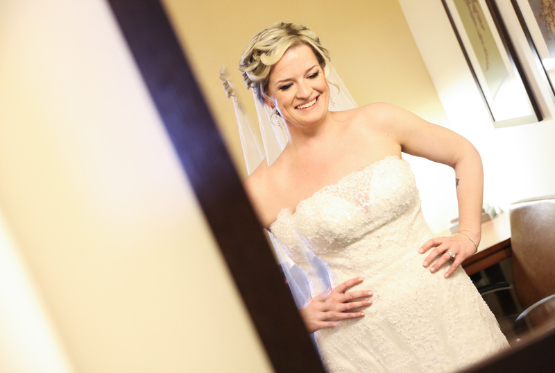 Wedding photography, a bride smiles in the mirror as she awaits her wedding ceremony.