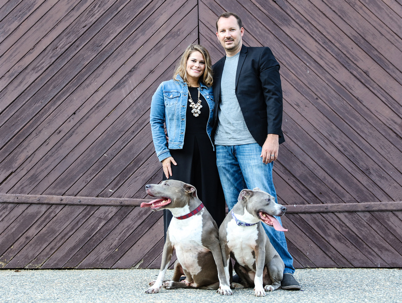 Family photography: a couple stands in front of brown barn doors with the pit bulls sitting at their feet.