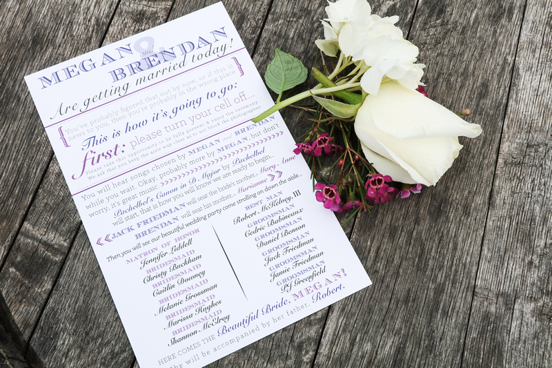Wedding photography, a wedding invitation sits on a wooden barrel next to white and purple flowers.